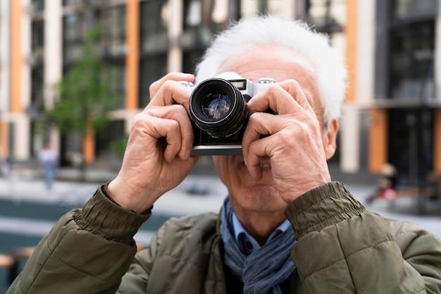 Stylowy starszy mężczyzna w mieście używający aparatu do robienia zdjęć