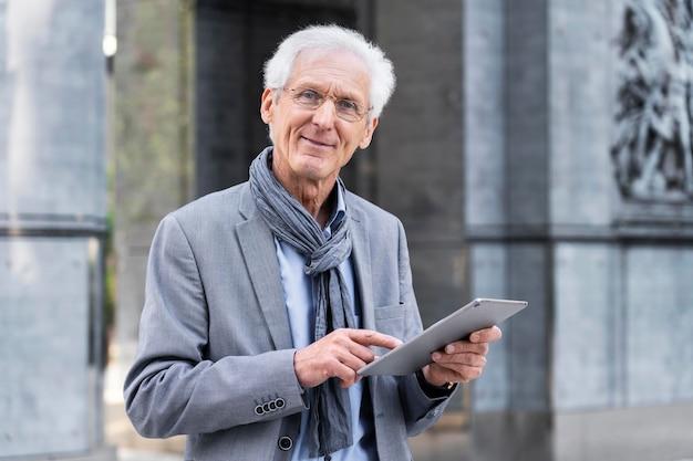 Stylowy starszy mężczyzna w mieście za pomocą tabletu