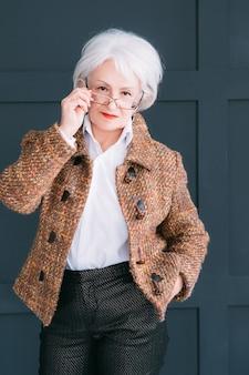Stylowy starszy pani portret. styl życia. pewność siebie i elegancję. pomyślna starsza kobieta pozuje w jesiennym stroju.