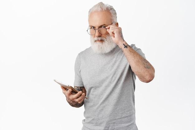 Stylowy staruszek w okularach z tatuażami, trzymający cyfrowy tablet, zakupy online za pomocą urządzenia, stojący w szarej koszulce na białej ścianie