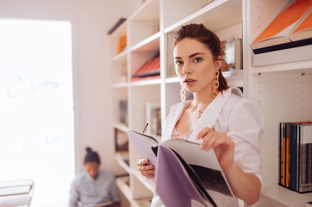 Stylowy strój. śliczna kobieta patrząca prosto w kamerę podczas pozowania w ulubionej księgarni