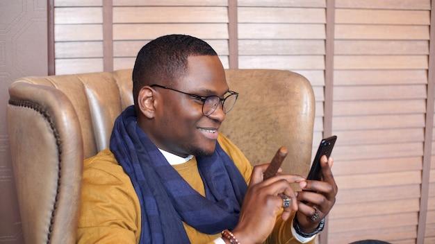 Stylowy szczęśliwy afroamerykanin siedzi na krześle z cygarem