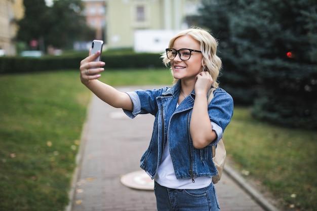 Stylowy szczęśliwy całkiem moda blondynka kobieta w dżinsach suite sprawia, że selfie na swoim telefonie w mieście rano