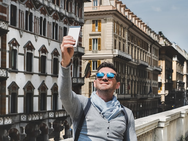 Stylowy, szczęśliwy człowiek ze smartfonem. wypoczynek, podróże, pozytywne