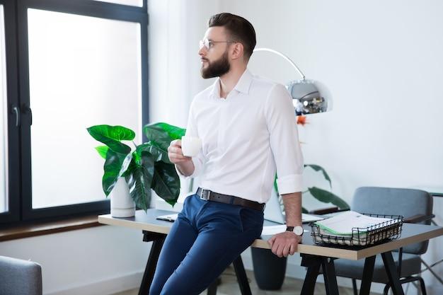 Stylowy szczęśliwy nowoczesny biznesowy mężczyzna w elegancki strój codzienny pozuje w biurze startowym podczas przerwy na kawę