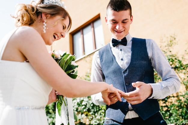 Stylowy szczęśliwy pan młody nosi złoty pierścionek na palcu panny młodej. ślub.