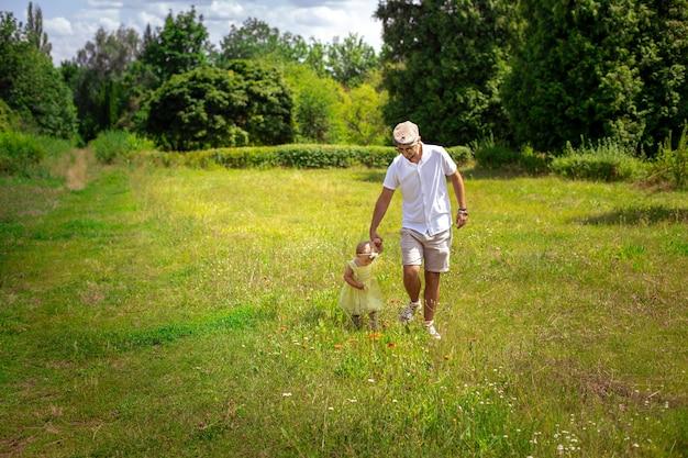 Stylowy tata spaceruje ze swoją małą córeczką na łące w okresie letnim
