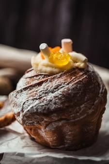 Stylowy tort wielkanocny z piankami i żelkami na ciemnym rustykalnym drewnianym tle, jajka przepiórcze leżą w pobliżu. sezonowe pozdrowienia wesołych świąt wielkanocnych. nowoczesny obraz wielkanocny szczęśliwy