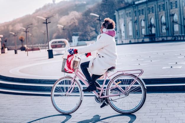 Stylowy transport. pozytywnie zachwycona dziewczyna korzystająca ze słuchawek podczas słuchania muzyki podczas spaceru