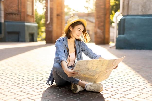 Stylowy turysta w kapeluszu sprawdzający lokalną mapę