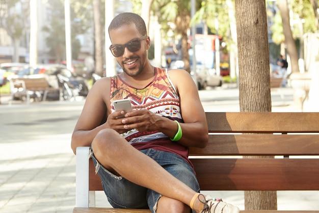 Stylowy turysta wypoczywa w parku, siedząc w cieniu drzew ze swoim gadżetem. afrykański mężczyzna surfuje po internecie w swoim telefonie komórkowym