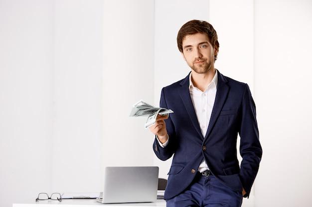 Stylowy udany młody biznesmen w swoim biurze, oprzyj się na stole, trzymając pieniądze, uśmiechając się, zawierając umowę z partnerem biznesowym