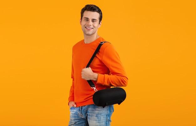 Stylowy uśmiechnięty młody człowiek w pomarańczowym swetrze, trzymając bezprzewodowy głośnik, szczęśliwy słuchając muzyki, zabawy na pomarańczowo