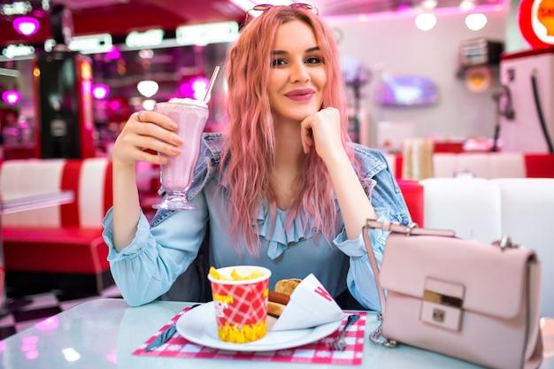 Stylowy wizerunek stylowej młodej ładnej kobiety z falistymi, niezwykłymi różowymi włosami i naturalnym makijażem, ubrana w uroczą niebieską sukienkę i dżinsową kurtkę, ciesz się smacznym amerykańskim obiadem.