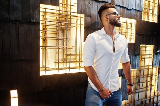 Stylowy wysoki mężczyzna w białej koszuli, dżinsach i okularach przeciwsłonecznych postawiony na lekkiej ścianie wewnątrz