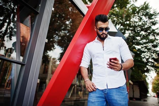 Stylowy wysoki mężczyzna w białej koszuli, dżinsach i okularach przeciwsłonecznych postawionych na ulicy miasta broda atrakcyjny facet patrząc na czerwony telefon.