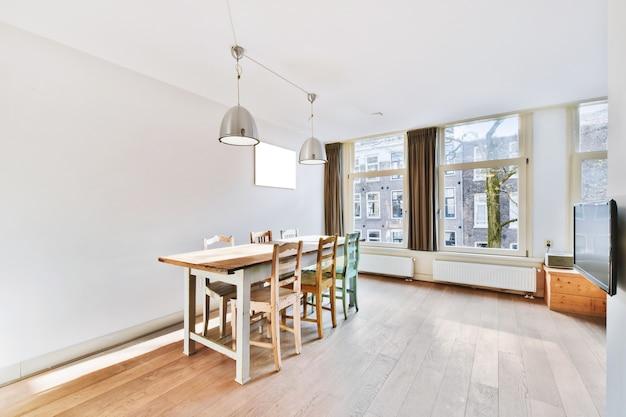 Stylowy wystrój domu ze strefą jadalną z lampami wiszącymi nad drewnianym stołem i krzesłami w nowoczesnym mieszkaniu z dużymi oknami i minimalistycznym designem