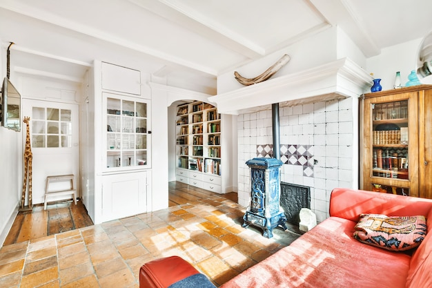 Stylowy wystrój salonu z jasnymi meblami i miękką wygodną kanapą i dywanem oraz tv na szafce w nowoczesnym mieszkaniu z otwartą kuchnią i białymi ścianami i kolumną.