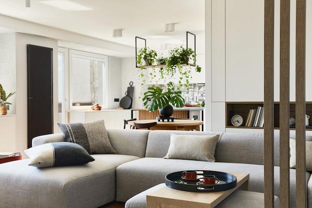 Stylowy wystrój salonu z szarą sofą i akcesoriami jadalnia w tle