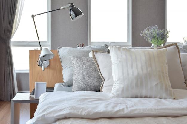 Stylowy wystrój wnętrz sypialni z białymi pasiastymi poduszkami na łóżku i dekoracyjną lampą stołową.