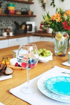 Stylowy wystrój wnętrza jadalni z talerzami, kubkami, kieliszkami i jedzeniem w stylu śródziemnomorskim