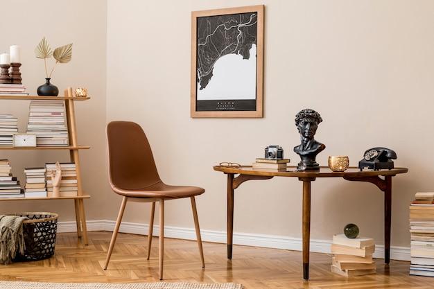 Stylowy wystrój wnętrza prywatnej sali bibliotecznej z mapą plakatową, brązowym krzesłem, drewnianym stołem, regałem, książkami i eleganckimi akcesoriami osobistymi. retro starodawny wystrój domu. beżowa ściana.