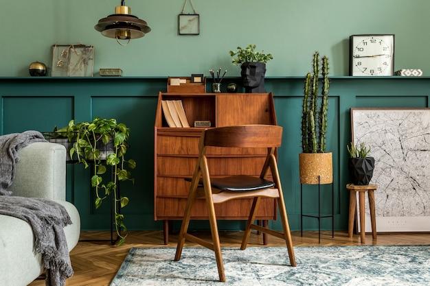 Stylowy wystrój wnętrza z drewnianą szafką w stylu retro, krzesłem, szarą sofą, roślinami, lampą wiszącą, dekoracją, mapami, stołkiem i eleganckimi akcesoriami osobistymi. nowoczesna koncepcja retro przestrzeni biurowej.