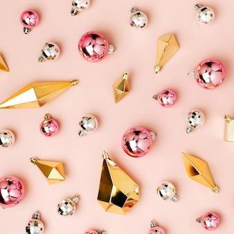 Stylowy wzór świąteczny z błyszczącymi kulkami i złotymi kryształkami na pastelowym różowym tle. płaski układanie, widok z góry