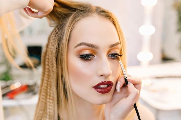 Stylowy zbliżenie portret pięknej młodej kobiety w salonie fryzjerskim przygotowuje się do imprezy. wykonywanie fryzur, makijażu, stylistka, profesjonalna, modna modelka, świat piękna, usługi fryzjerskie