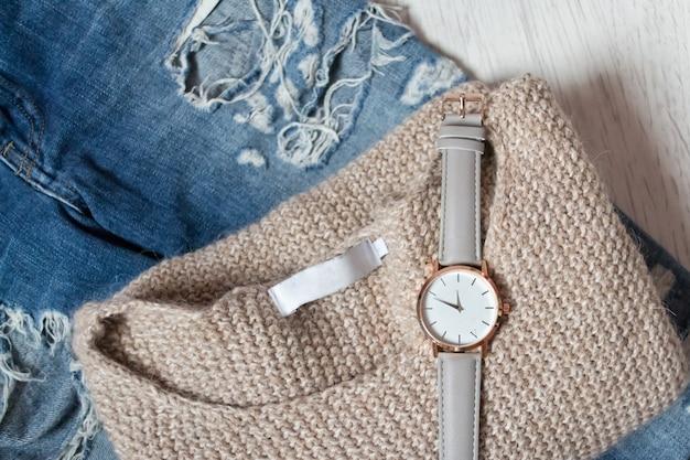 Stylowy zegar na swetrze i podarte dżinsy