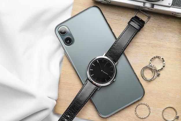 Stylowy zegarek, pierścionki i telefon komórkowy
