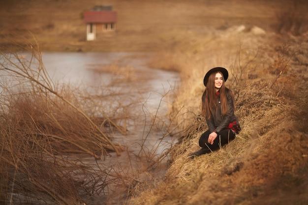 Stylu życia portret młoda kobieta odpoczywa w czarnego kapeluszu