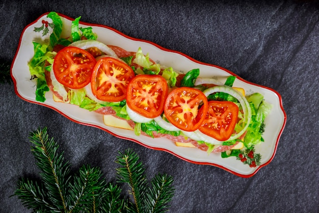 Sub kanapka z salami, serem i warzywami na długim talerzu