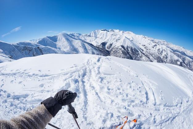 Subiektywny osobisty widok narciarza alpejskiego na zaśnieżonym stoku gotowym do jazdy na nartach