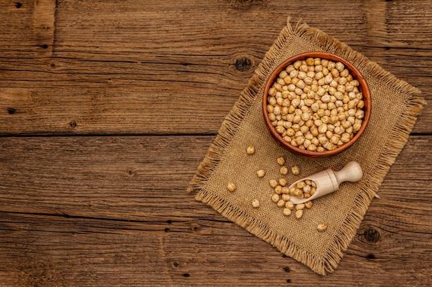 Sucha ciecierzyca w ceramicznym pucharze na starym drewnianym stole. tradycyjny składnik do gotowania humusu