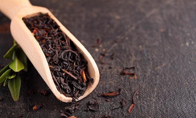Sucha czarna herbata na czarnym tle