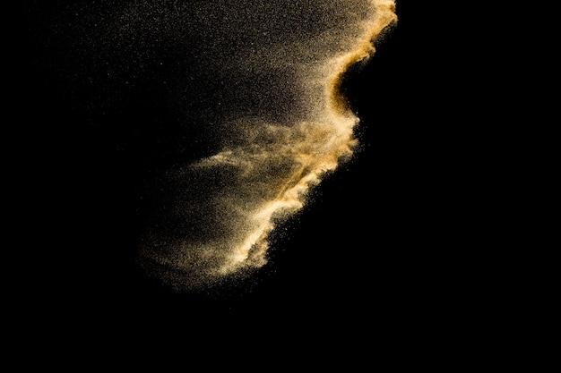 Sucha eksplozja piasku rzecznego. złoty kolor piaska pluśnięcie przeciw czarnemu tłu.