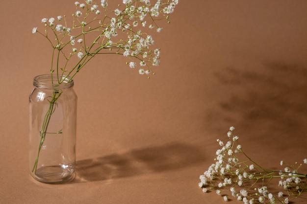 Sucha gałąź kwiat na jasnobrązowym tle. trend, minimalistyczna koncepcja z widokiem z boku z ciemnym cieniem