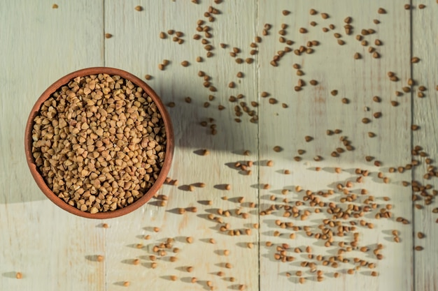 Sucha gryka w brown glinianym pucharze na drewnianym stole. bezglutenowe ziarno dla zdrowej diety, widok z góry