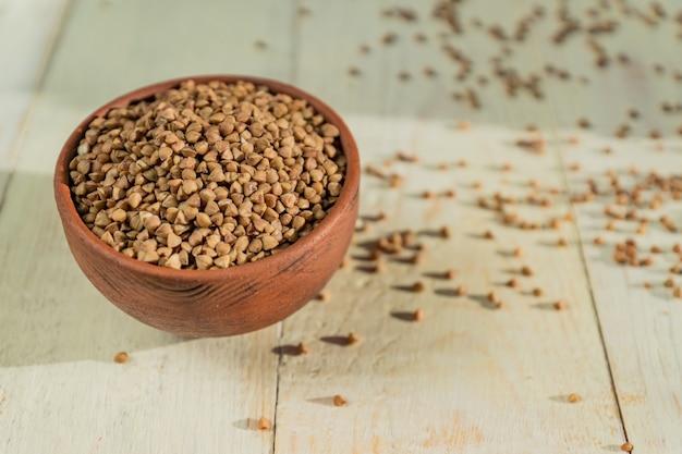 Sucha gryka w brown glinianym pucharze na drewnianym stole. bezglutenowe ziarno dla zdrowej diety