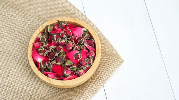 Sucha herbaciana menchii róża na białym drewnianym stole.
