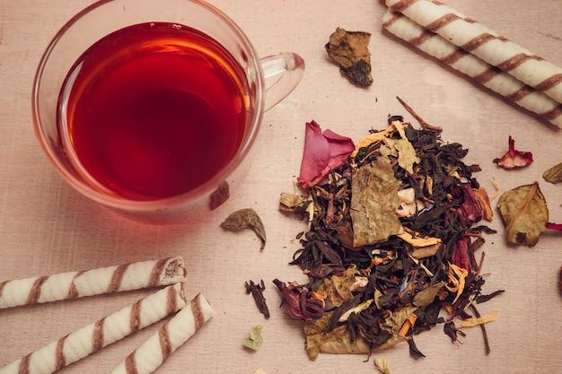 Sucha herbata, filiżanka, cukierki na drewnianym tle