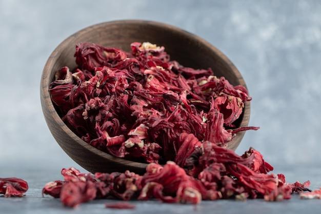 Sucha herbata hibiskusowa w drewnianej misce.