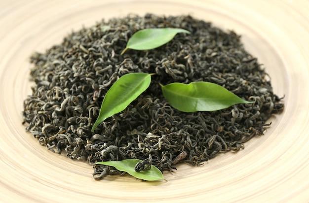 Sucha herbata z zielonymi liśćmi w beżowym talerzu, zbliżenie