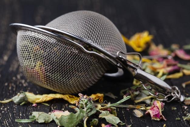 Sucha herbata ziołowa leży na drewnianym stole