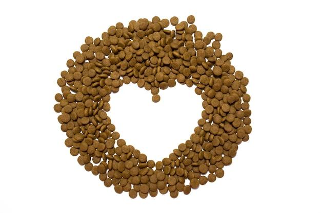 Sucha karma dla kotów i psów na białym tle. serce z jedzenia. zdjęcie wysokiej jakości