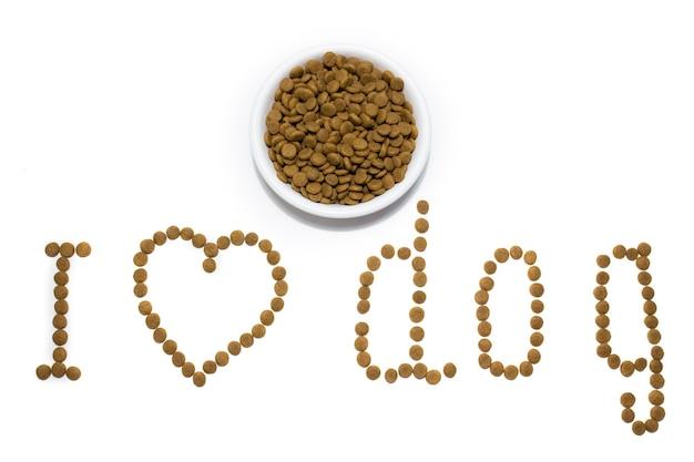 Sucha karma dla kotów i psów w białej misce. serce z jedzenia. napis kocham psy. studio białe tło. zdjęcie wysokiej jakości