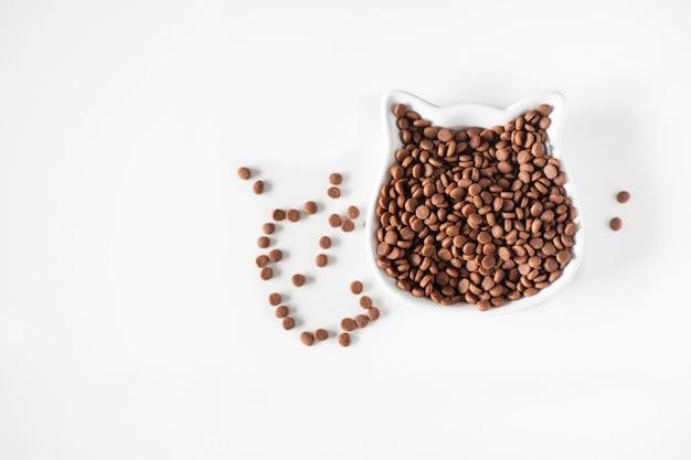 Sucha karma dla kotów w białym naczyniu dla kota na białej powierzchni. widok z góry, miejsce na kopię