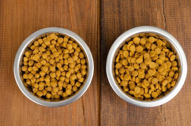 Sucha karma dla kotów w metalowej misce na powierzchni drewnianych