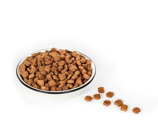 Sucha karma dla zwierząt domowych w białej misce ceramicznej na białym tle na białej powierzchni. skopiuj miejsce